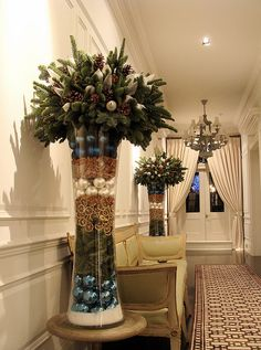 fill a tall vase with layers of Christmas ornaments and trim, top with evergreen arrangement