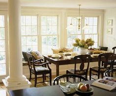 """Breakfast banquette with rectangular table & """"farmhouse"""" windows."""