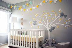 decoração quarto de bebê com bandeirinhas de tecido branca, amarela e azul penduradas no teto, parede cinza com adesivo de árvore com coalas