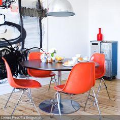 Orangefarbene Retro-Stühle um den runden Esstisch bilden das Herzstück des Esszimmers. Die Industrieleuchte rundet das Retro-Ambiente ab.