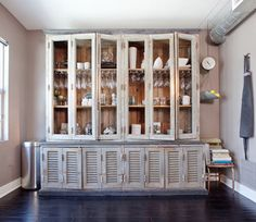 An old 1800s hutch from a library in Venice, Italy, serves as storage for dishes and glassware in the kitchen.