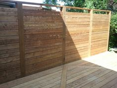 A privacy wall creates a courtyard space on this roomy new deck. Its all done with Sienna brown pressure treated lumber and hidden fasteners