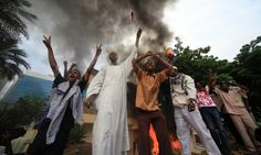 Sudanese demonstrators stand in front of the burning German embassy in Khartoum after Friday prayers. Sudanese demonstrators broke into the US and German embassy compounds in Khartoum and raised Islamic flags.