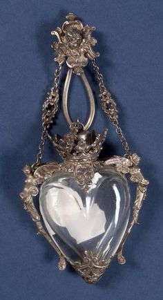 century heart shaped Chatelaine scent bottle with silver mounting of angels, coronet-form neck enclosing stopper, suspended from chain with chatelaine clip centered by cherub. Antique Perfume Bottles, Vintage Bottles, Metal Nobre, Antique Jewelry, Vintage Jewelry, Beautiful Perfume, Schmuck Design, Heart Shapes, Designer