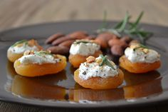 8 whole dried apricots 2 tsp goat cheese freshly ground black pepper 4 salt-roasted whole almonds, roughly chopped 8 fresh rosemary leaves