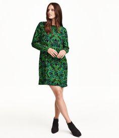 Lige skåret kjole i sval, vævet kvalitet med trykt mønster. Den har åbning i ryggen, som går helt ned til taljen. Lukning bagpå. Lange ærmer. Uden for.