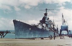 The U.S. Navy New Orleans-class heavy cruiser USS Minneapolis (CA-36) at Pearl Harbor Navy Yard, Hawaii, on 11 April 1943, after being fitted with a new bow. She had lost her original bow in the Battle of Tassafaronga, off Guadalcanal on 30 November 1942. Note the New Mexico-class battleship in the left distance.