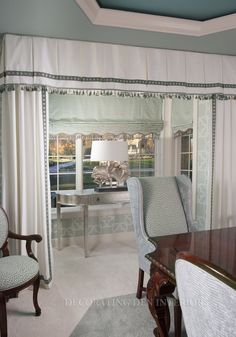 Roman shades in aqua geometric fabric and scalloped and fringed. Floor length panels in luxurious cotton with sun decorative tape. Box pleat valance with sun tape and tassel fringe containing chrome tubes holding aqua and cream tassels. Traditional with modern accents.
