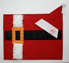 Santa's New Suit Placemats & Napkins--so cute and so easy. The napkin folds into Santa's Hat and the pompom is on a clip. Use fake fur or regular quilter's cotton for the white strip! Pattern is available at www.craftsy.com