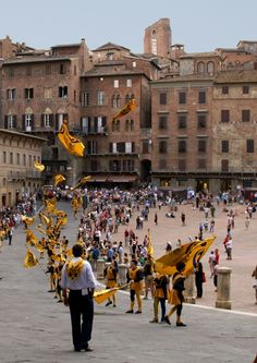Sunday Parade in Siena - Parade of one of the neighborhoods of the city of Siena, showing off by throwing their flags up. This parade is held each week, where one of the neighborhoods march to the Piazza del Campo, now regarded as one of the most beautiful civic spaces in Europe