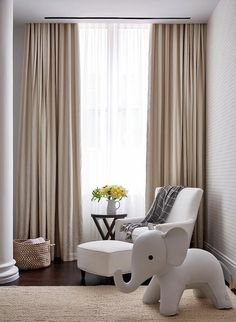 Beautiful white and beige nursery boasts a window dressed in sheer white curtains layered behind beige striped curtains hung behind a white corner chair paired with a matching ottoman positioned between a light gray felt elephant placed on a jute rug and a round side table.
