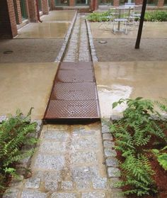 Waltham Watch Factory. Cobblestone runnels direct water away from buildings and into the rain gardens, also providing the courtyards with an important aesthetic element. Richard Burck Associates