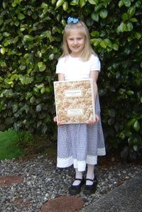 """Madeleine had her """"meeting"""" with the DRE at our parish this morning. It went well, and she is eagerly awaiting April 27!!! Here she is with her First Holy Communion Notebook that has only a couple of pages left to..."""