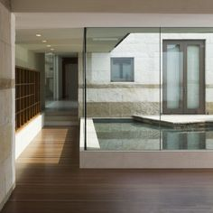 Modern home design with abutting pond. Love the sitting area off French doors and the glass halls.