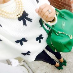 Black skinny jeans, white sweater with black bows, green bag, pearls, green heels.