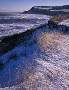 A view looking south from near Boggle Hole across windswept snow covered grassland and white capped waves towards the impressive headland of Ravenscar