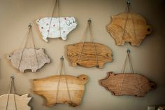pig cutting board collection! Displayed on my kitchen wall, hanging in two loops of jute string on old rusty washers. Non-damaging way to display these antiques! The perfect way to display my pigs.