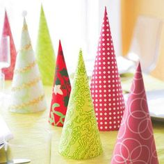 "Turn holiday-theme scrapbooking papers into an inexpensive tabletop display. Cut and fold papers to create simple cone ""trees"" of different sizes. Secure seams with double-sided tape"