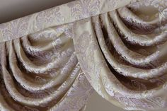 """Custom made swag valance curtains. The fabric is """"Gold Ivy"""" - light gold brocade satin with white and lavender color floral patterns. The light bounces between the curvaceous swags and drapes, luxurious yet subtle."""