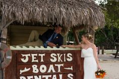 Bride and groom by boat rental stand at beach wedding. Photo taken by Caterson Media caterson.com at Coconut Cove Resort in Islamorada, FL