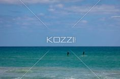 Standing on Surf Boards - Two men standing on surf boards row their way through the water in Palm Beach, Florida.