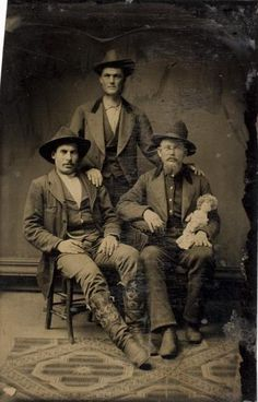 ca. 1875, [tintype portrait of three cowboy-esque gentlemen, one with a doll] via the International Center of Photography