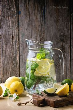 Pitcher of Lemonade - Glass pitcher of homemade lemonade, served with whole and sliced lemons, limes and mint over wooden table with wooden background. Detox Drinks, Healthy Drinks, Lemon Water Benefits, Drinking Lemon Water, Water With Lemon, Fruit Photography, Breakfast Photography, Homemade Lemonade, Lose Weight