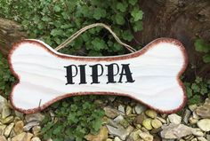 A wooden bone shape name sign which is personalised for your dog made from reclaimed wood and comes with jute string ready to hang over your dogs bed, kennel or bowls. Hand Painted in a choice of colours and 2 finishes indoor and outdoor. Size 30cm x 12cm  £7.50 available from www.dreamyhomes.co.uk