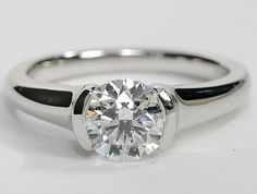 Modern style solitaire engagement ring with the diamond in a half bezel setting. This is a simple solitaire setting, but with a modern flair to it.