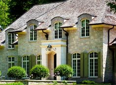 European round-top dormers, French windows on the entire ground floor, a stone facade and a symmetrical exterior...everything I love!