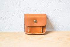 コインケースのキャメル色のステッチが印象的な二つ折りの革財布。手縫いの麻のステッチは工房で一つ一つ手縫いしたもの。植物性タンニン鞣しの革を使い麻糸でしっかり縫いあげているので丈夫です。また、名入れにも対応しているのでプレゼントやギフトにオススメです。