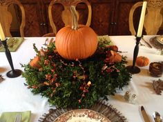 Boxwood wreath and a pumpkin....add a few sprigs and some ribbon.....voila! Centerpiece for Thanksgiving! Shared this idea with a friend and she created this lovely tablescape !