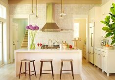 Open kitchen by Angie Hranowsky with wood floor, simple white cabinets, squared…