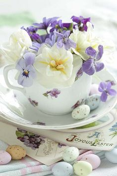Teacup filled with spring flowers, including pansies and violets. Victorian postcards arranged underneath.