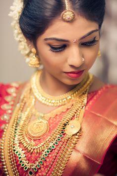 rust orange and red bridal kanjivaram , south Indian bride with layered gold jewellery,