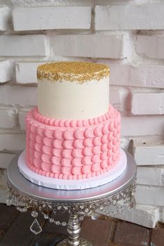 Pink and gold themed first birthday cake for a very special little lady! Bottom tier is chocolate cake filled with salted caramel and topped with pink buttercream, top tier is fresh raspberry cake filled and topped with vanilla buttercream and gold sprinkles