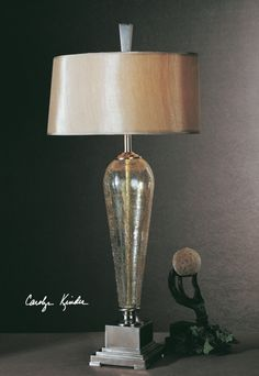 This lovely iridescent, crackle glass table lamp has brushed, warm nickel accents and a gold silken, oval drum shade.