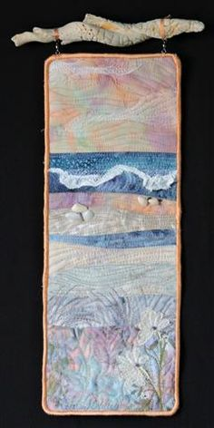 Beach series #33.  Small art beach quilt by Eileen Williams.  Hanging from found shell fragment and embellished with vintage lace and found shells.