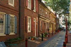 Tiny street, bollards, trees that create a natural weather canopy, historic brick and lighting.