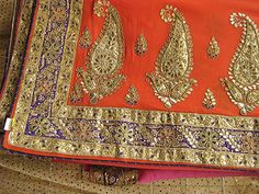 Georgettes, chiffons and crepes are shaded in bright oranges, hot pinks, reds and purples. Each saree has two different colors that merge to form a third color. The border, which is richly embellished with Rajasthani gota patti work, is also suffused with a third contrast color like green or purple, so as to match with kundan jewelry that is inlaid with meenakari work.
