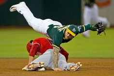 Handstand -  Grant Green (bottom) of the Los Angeles Angels of Anaheim is tagged out attempting to steal second base by Brett Lawrie of the Oakland Athletics during a game on Aug. 31 in Oakland, Calif. -  © Jason O. Watson/Getty Images