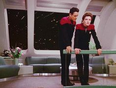Janeway and Chakotay. They literally have the entire room to talk in private but by all means stand only inches from each other.