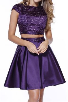This two piece prom dress features a fitted cropped top and a satin flared skirt. The cap sleeves add a bit of coverage, while the keyhole back cut out gives this look a bit of sexy! For added sparkle