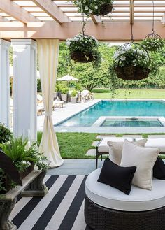 Rectangular swimming pool surrounded by a patio pergola with outdoor drapery