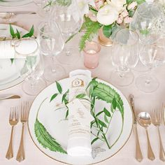 Resting atop each botanical-inspired plate was a gold-foil-printed menu rolled around a linen napkin and tied with gold thread, a sprig of greenery, and a place card. ✨ #marthaweddings