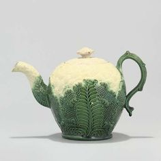 AN ENGLISH CREAMWARE CAULIFLOWER-MOULDED TEAPOT AND COVER  CIRCA 1760, PROBABLY WEDGWOOD  Naturalistically moulded, with foliate handle and cabbage-leaf spout  5 1/8 in. (13.2 cm.) high (2)