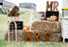 """Rustic outdoor fall wedding ceremony decor idea - hay bales + metal letters to spell out """"Mr. & Mrs."""" displayed with pumpkins {Michelle Lea Photographie}"""