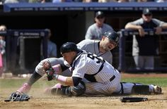 GAME 34: Sunday, May 13, 2012 - Seattle Mariners' Jesus Montero, top, is tagged out at home plate by New York Yankees catcher Russell Martin on a double play during the sixth inning of a baseball game at Yankee Stadium in New York. (AP Photo/Seth Wenig)