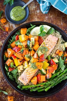 Roasted Salmon + Veggie Bowl – Healthy salmon and a rainbow of vegetables are cooked on one sheet-pan and served on top of a bed of arugula/spinach and quinoa. Topped off with some basil pesto and a squeeze of lemon. Perfect for an easy weeknight dinner.