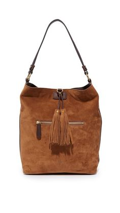 A roomy Frye tote in rich suede. A large tassel hangs from the magnetic top. Zip front pocket. Lined, 3-pocket interior. Sling strap. Dust bag included.